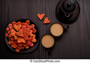 Red heart-shaped cookies, two cups of tea with milk and teapot. Valentine's Day