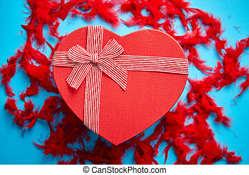 Red, heart shaped gift box placed on blue background among ...