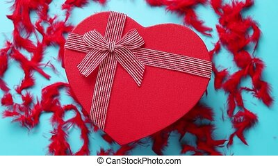 Red, heart shaped gift box placed on blue background among...