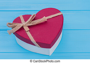 Red heart shaped gift box with bow.