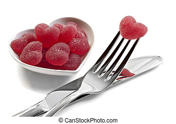 Red heart shaped jelly sweets with knife and fork on white...