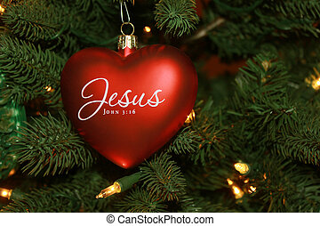 Red heart shaped Jesus Christmas ornament on tree