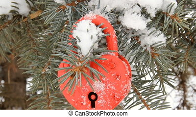 Red heart-shaped lock on the branch