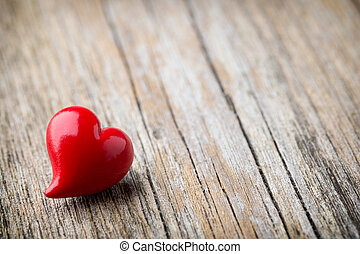 Red heart-shaped on a wooden background.