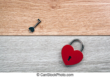 red heart shaped padlock plus a key on a wooden background
