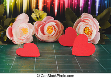 Red heart sign with flowers on background.