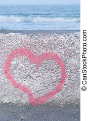Red heart spray painted on wall in background of the sea