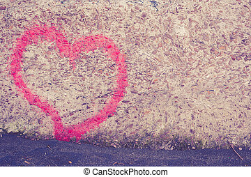 Red heart spray painted on wall in background