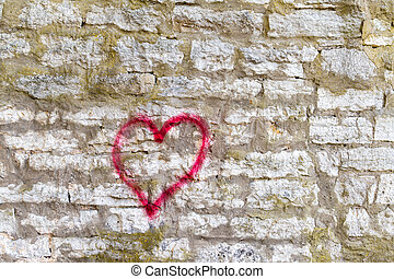 Red heart symbol painted on brick wall.