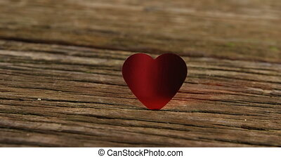 Red heart tuck in the wooden plank 4k