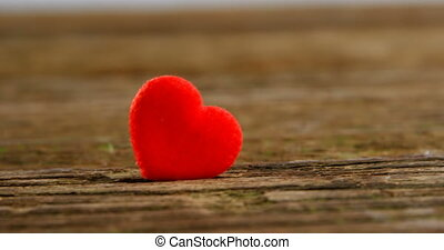 Red heart tuck in the wooden plank. Valentines day concept 4k
