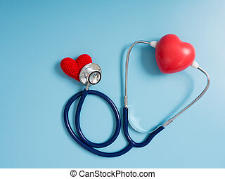 red heart using deep blue stethoscope on the blue background for hear their other heart. Concept of love and caring patient by the heart. Copy space for the text and contents