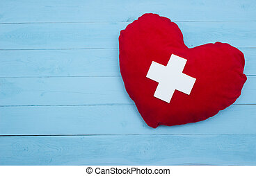 red heart with a white cross on blue background