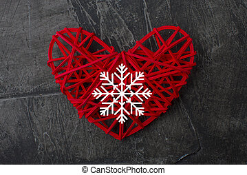 Red heart with a white snowflake on a dark background