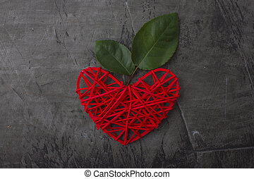 Red heart with green leaves on a dark background. Blooming love. Valentine's day or wedding. Romance. Wedding