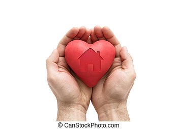 Red heart with imprinted house shape in man's hands.
