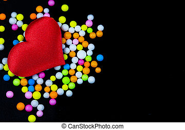 Red heart with multicolored foam beads on a dark black background
