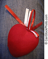 Red heart with red and white stripes on the jeans background
