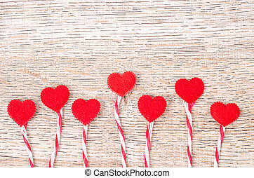 Red heart with rope on wooden background.