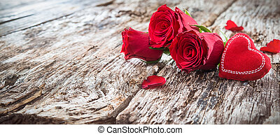 Red heart with roses on a rustic wooden background
