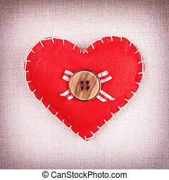 Red heart with wooden button and bow