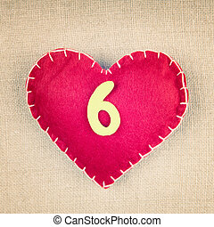 Red heart with wooden number 6 on vintage fabric background