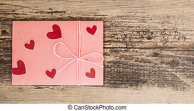 Red hearts and pink envelope on wooden background