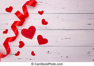 Red hearts and ribbon on a white wooden background. Top view, free space for text. Valentine's Day, love.