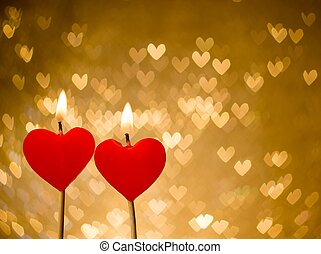 red hearts candles on golden hearts bokeh as background