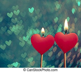 red hearts candles on vintage hearts bokeh as background