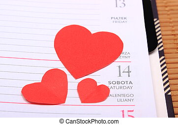 Red hearts for valentines day on calendar