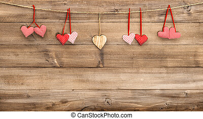 Red hearts hanging on wooden background. Valentines Day