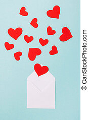 Red hearts in an open white envelope