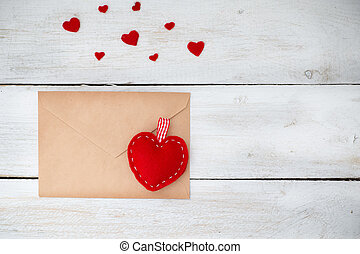red hearts lie with an envelope on a white wooden background