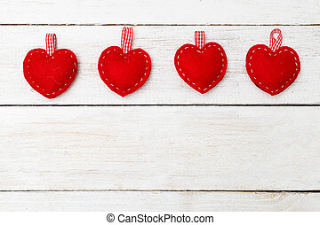 Red hearts of felt on a white wooden background. Valentine concept
