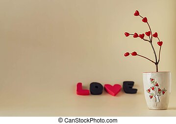 Red hearts on a branch in a ceramic vase and the letters love. Free space for text.