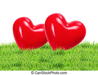 Red hearts on green grass background