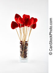 Red hearts on wooden sticks and chestnuts in glass