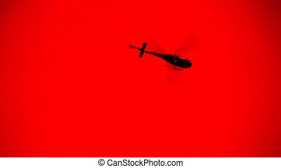 Red helicopter. - A helicopter flies overhead. Sky coloured...