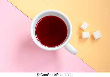 Red hibiscus tea in a white cup with pieces of sugar on orange and pink background