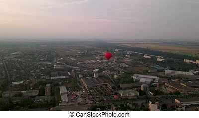 Red hot air balloon flying over buildings in industrial zone...
