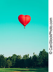 Red hot air balloon in the shape of a heart against the blue sky