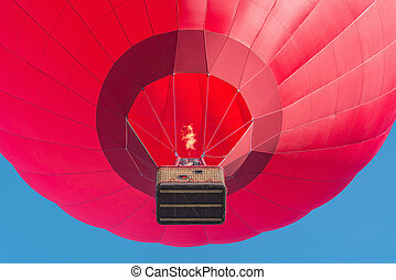 Red hot air balloon on blue sky background.