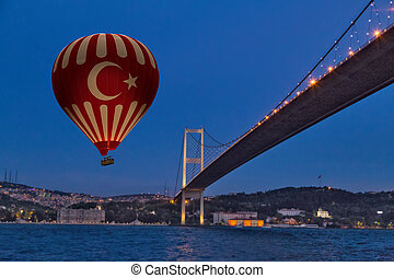 Red Hot Air balloons flying over Bosphorus Bridge at night. Istanbul, Turkey