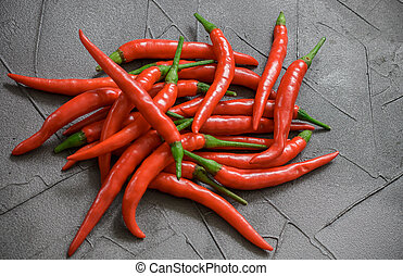Red hot chili pepper on black surface