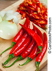 Red hot chili pepper with Onions on the Chopping Block