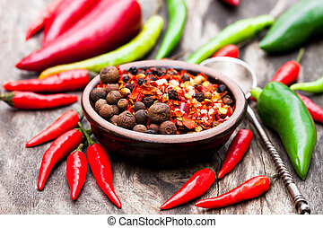 Red hot chili peppers and other spices in a small plate on wooden background