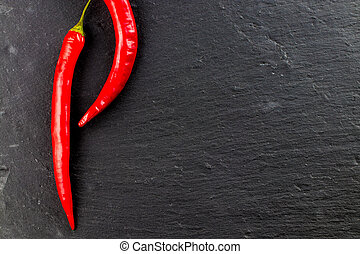 Red hot chili peppers and peppercorns on black background, top view with copy space