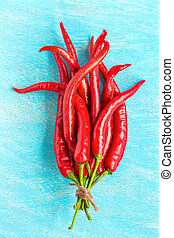 Red hot chili peppers on blue wooden background, top view