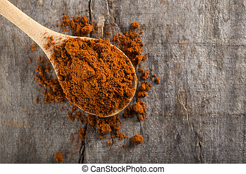 Red hot paprika powder on wooden spoon